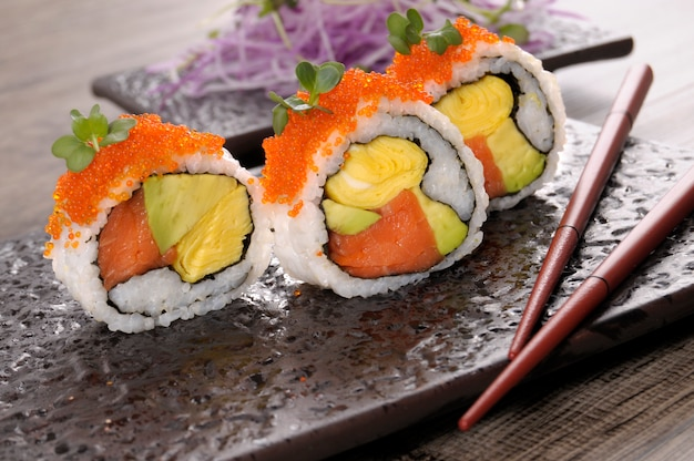Rolo de sushi de califórnia com pauzinhos