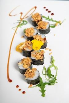 Rolo de sushi de camarão com cebola frita por cima. imagem vertical