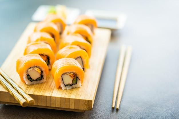Rolo de sushi de carne de peixe salmão maki na placa de madeira