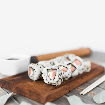 Rolo de sushi delicioso com sementes de gergelim, dispostas na bandeja de madeira
