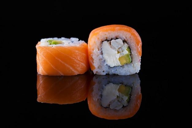 Rolo de sushi delicioso da califórnia em um fundo preto com reflexão