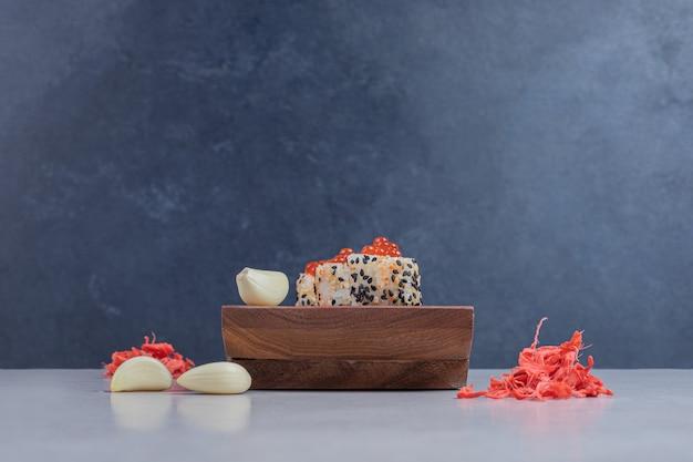 Rolo de sushi do alasca com gengibre em conserva na placa de madeira.
