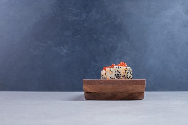 Rolo de sushi do alasca na placa de madeira com caviar vermelho.