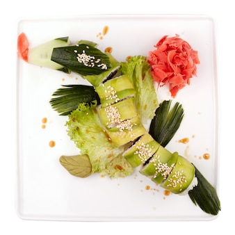 Rolo de sushi dragão verde no prato branco isolado no branco