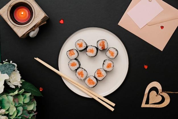 Rolo de sushi em forma de coração, no prato. postura plana.