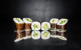 Rolo de sushi feito de Nori, arroz marinado, gergelim branco, pepino. T