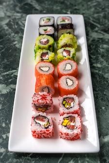 Rolo de sushi fresco feito definido na chapa branca. cozinha tradicional japonesa.