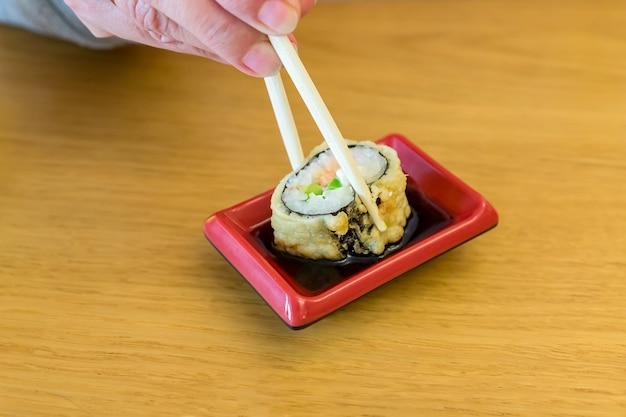 Rolo de sushi frito quente mergulhado em molho de soja em uma mesa de madeira