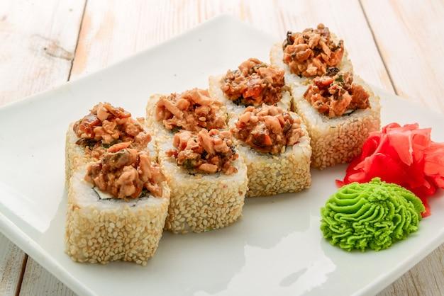 Rolo de sushi japonês coberto com fatia de salmão picante