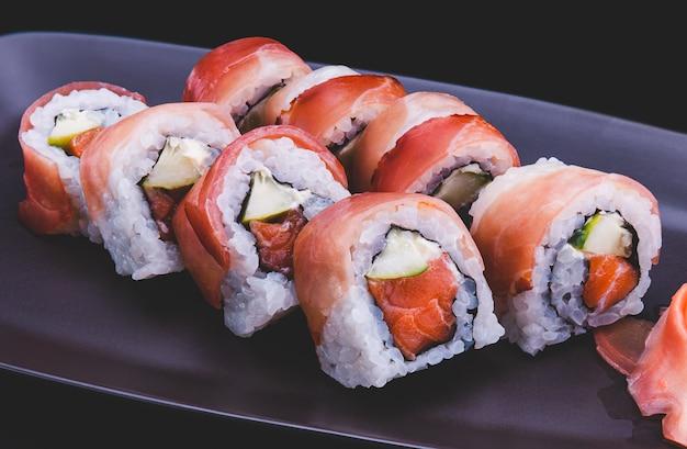 Rolo de sushi japonês com fatia de presunto cru cortado no prato