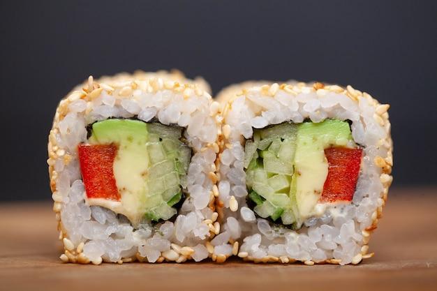 Rolo de sushi japonês com salmão e pepino no escuro