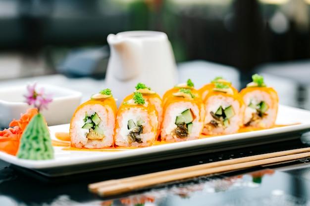 Rolo de sushi laranja com pepino e peixe, guarnecido com tobiko verde