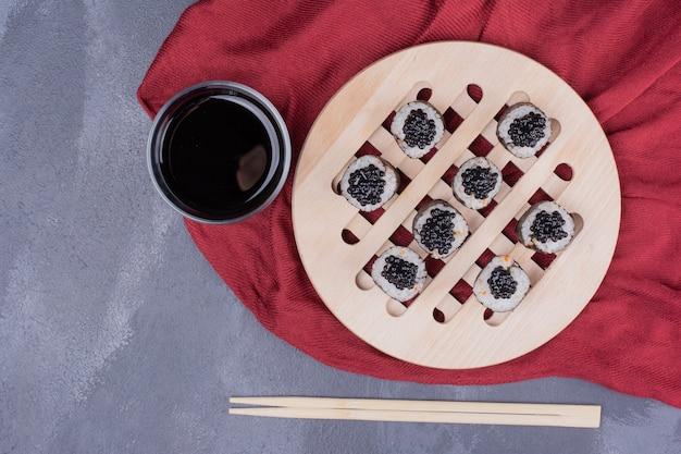 Rolo de sushi maki tradicional com pauzinhos e molho de soja na toalha de mesa vermelha.