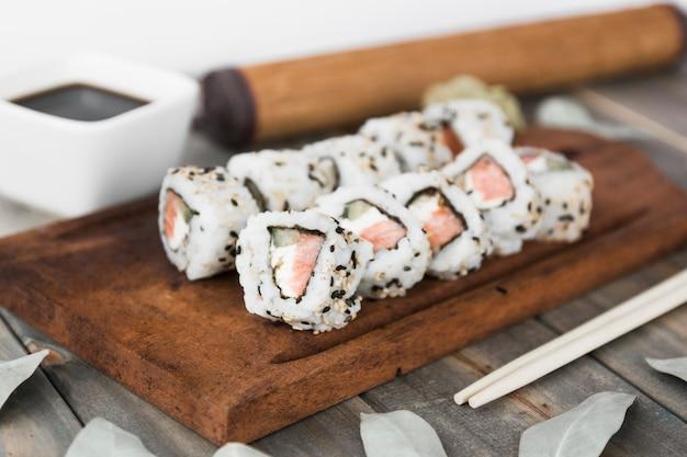 Rolo de sushi na bandeja de madeira com molho de soja e picar paus
