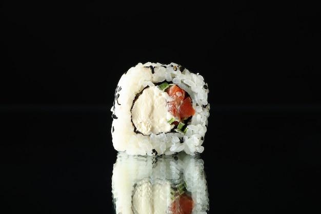Rolo de sushi no espelho preto, close-up
