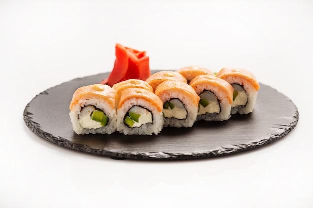 Rolo de sushi philadelphia em uma pedra redonda preta.