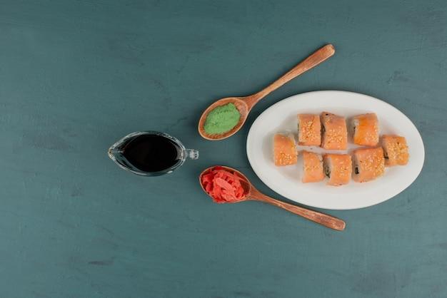 Rolo de sushi phildelphia com gengibre em conserva, molho de soja e wasabi na mesa azul.