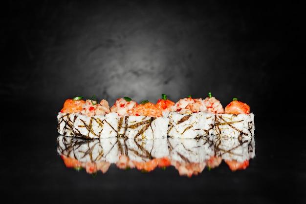 Rolo de sushi tobica feito de nori, arroz marinado, queijo, pepino, abacate, salmão