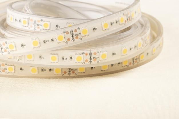 Rolo de tira de led em close-up de fundo amarelo, iluminação decorativa quente.
