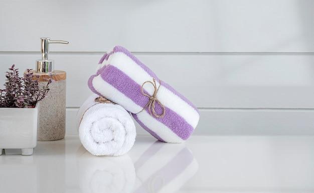 Rolo de toalha branca de spa amarrada com corda de cânhamo na mesa de balcão branca