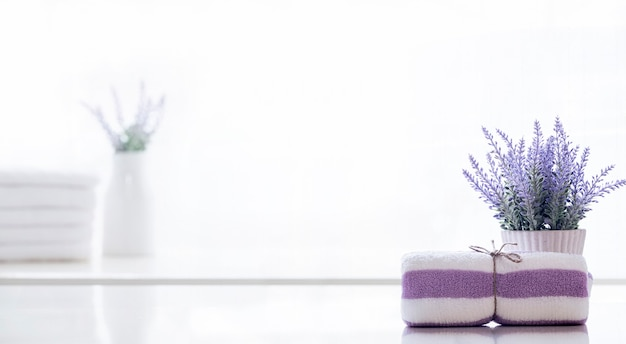 Rolo de toalha spa amarrado com corda de cânhamo na mesa de balcão branca.