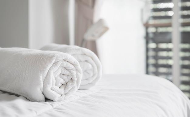 Rolo de toalhas de banho limpas brancas na cama no quarto de hotel. copie o espaço.