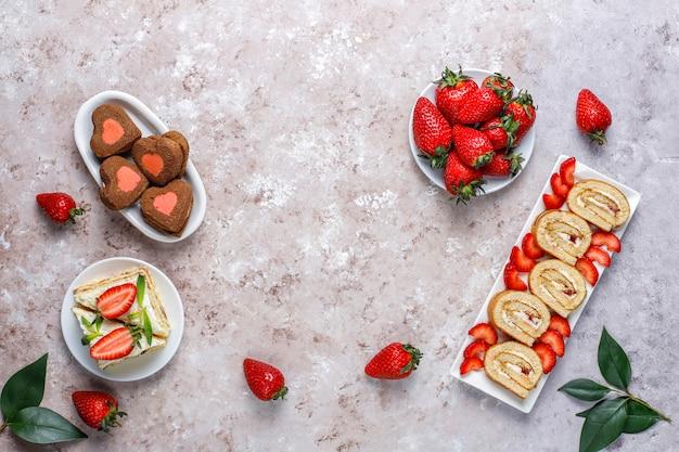 Rolo delicioso bolo de morango, biscoitos em forma de coração, fatias de bolo com morangos frescos, vista superior