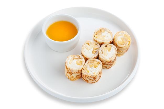 Rolo doce com creme de banana e manteiga. servido com mel. sobremesa. em uma placa de cerâmica branca. fundo branco. isolado