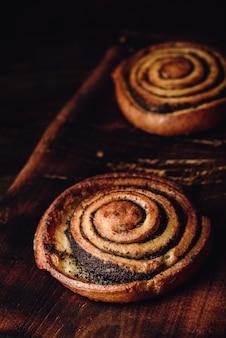 Rolo doce com sementes de papoula em superfície de madeira rústica