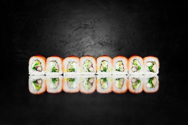 Rolo dragão vermelho feito de salmão defumado, nori, arroz em conserva, queijo, uagagi poleiro