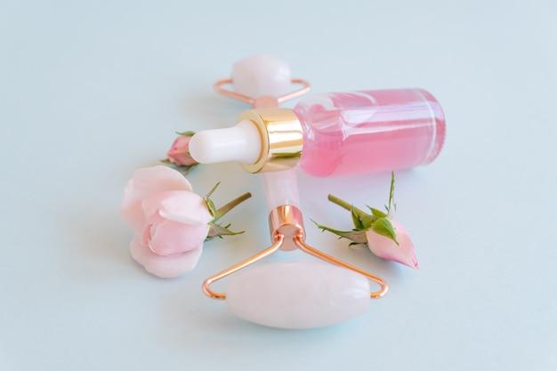 Rolo facial de jade e óleo essencial de rosa para terapia de massagem facial de beleza, itens para tratamento em casa com ferramentas anti-envelhecimento para cuidados com a pele e soro facial em fundo azul