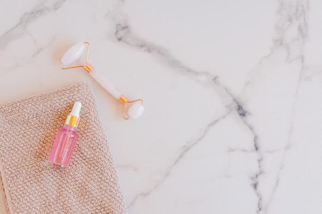 Rolo facial de jade e óleo essencial de rosa para terapia de massagem facial de beleza, itens para tratamento em casa com ferramentas anti-envelhecimento para cuidados com a pele e soro facial em fundo de mármore.