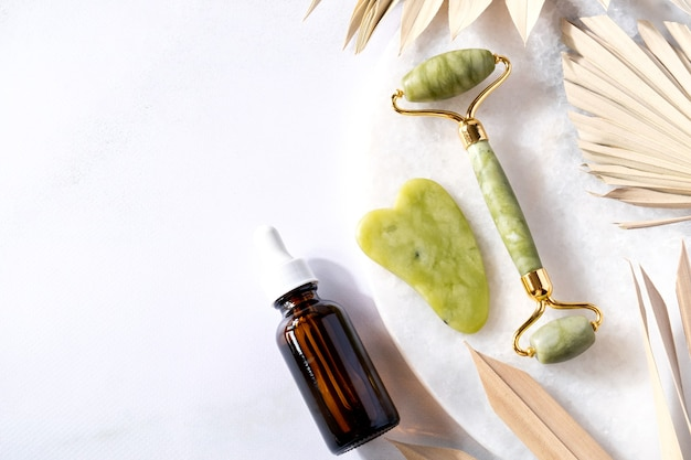 Rolo facial de óleo de garrafa de produtos cosméticos e massageador gua sha vista superior spa relax