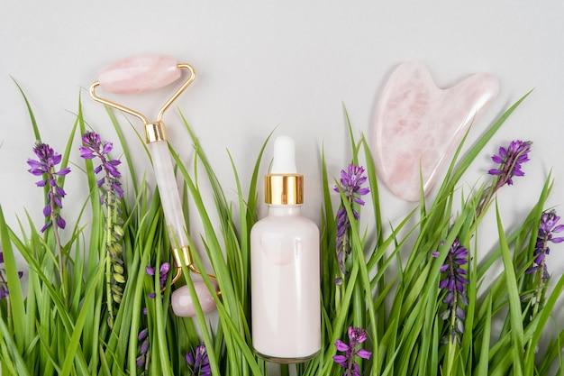 Rolo facial de quartzo rosa cristal, ferramenta de massagem gua sha e colágeno anti-envelhecimento, soro em frasco de vidro entre a grama verde, flores roxas. massagem facial para levantamento natural, conceito de beleza.