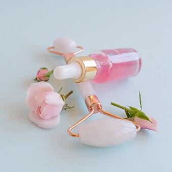 Rolo facial de quartzo rosa cristal, frasco conta-gotas cosmético com água de rosas ou óleo essencial sobre fundo azul. massagem facial para levantamento natural, close-up do conceito de beleza.