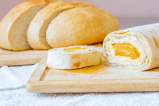 Rolo fatiado de pão pita armênio com recheio de cenoura em uma placa de madeira. pão branco fatiado no fundo. no quadro estão dentes de alho. guloseima caseira saborosa e saudável.
