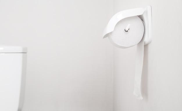 Rolo higiênico de papel branco em suporte de plástico.