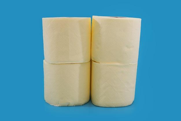 Rolos amarelos de papel higiênico em um fundo azul.