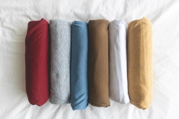Rolos coloridos de t-shirt sobre o conceito de cama branca de pronto para viajar.