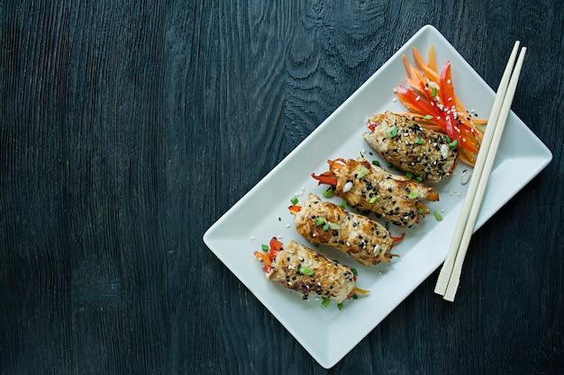 Rolos com peito de frango fresco com verduras, fatias de cenoura, pimentão em uma tábua escura.