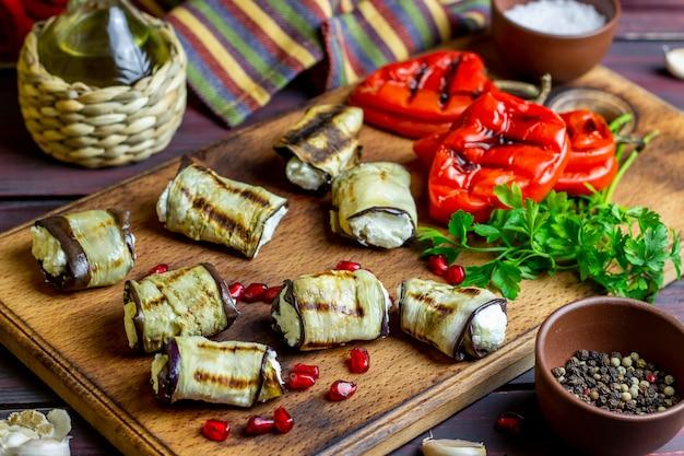 Rolos de berinjela com queijo em um fundo de madeira. alimentação saudável.