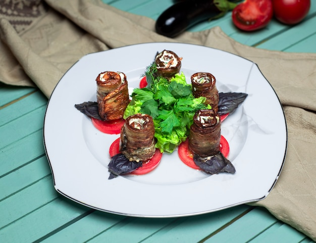 Rolos de berinjela com salada de legumes no prato branco.