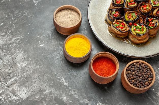 Rolos de berinjela recheada de baixo em um prato oval com especiarias diferentes em fundo cinza