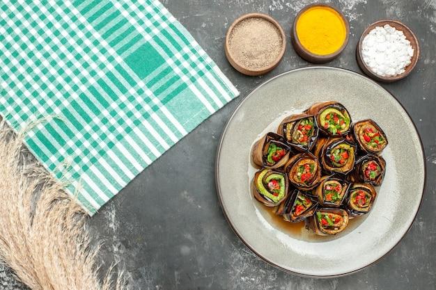 Rolos de berinjela recheada de cima em prato oval branco toalha de mesa branco turquesa com especiarias diferentes na superfície cinza