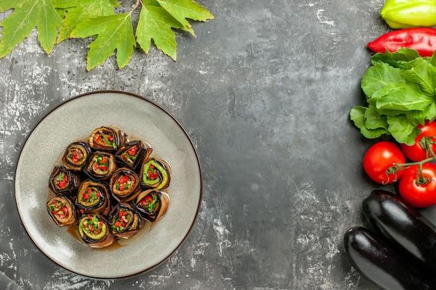 Rolos de berinjela recheada de cima em um prato branco de vegetais na superfície cinza