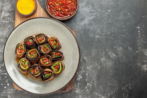 Rolos de berinjela recheada de cima em um prato oval branco açafrão em uma tigela sobre uma tábua de servir de madeira com alça adjika em fundo cinza