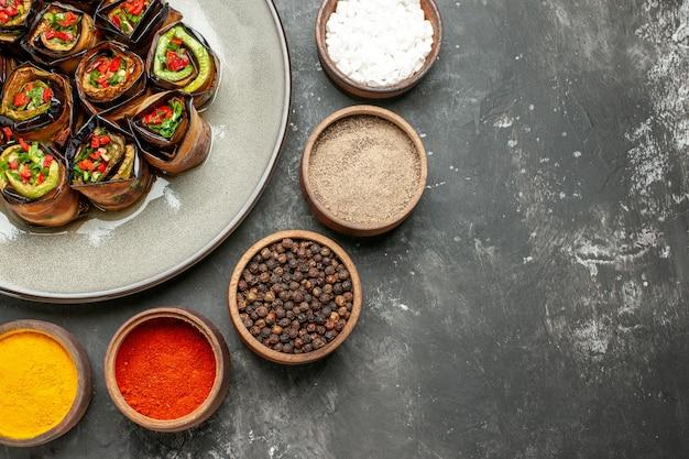 Rolos de berinjela recheada de cima em um prato oval branco, temperos diferentes em pequenas tigelas em um fundo cinza.