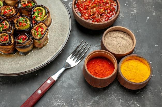 Rolos de berinjela recheada de frente em prato oval branco garfo óleo adjika em tigela pequena especiarias diferentes em fundo cinza