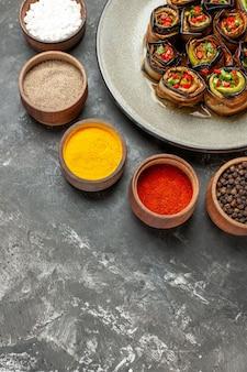 Rolos de berinjela recheada de frente em um prato oval branco, temperos diferentes em pequenas tigelas em um fundo cinza.