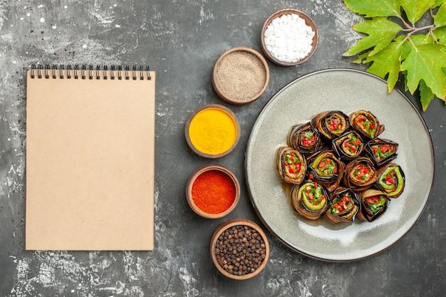 Rolos de berinjela recheada de vista de cima em um prato oval branco com especiarias diferentes um caderno em fundo cinza